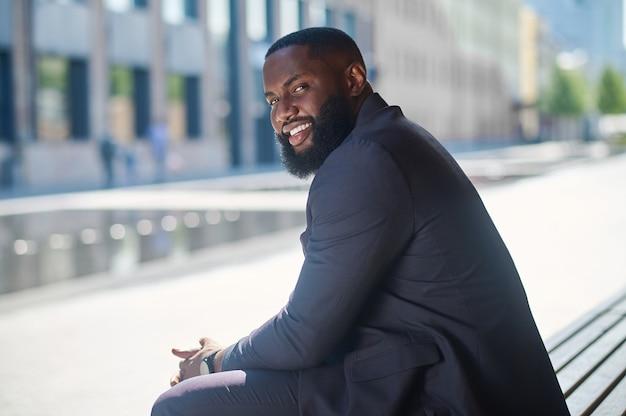 Um homem afro-americano de terno elegante sentado no banco