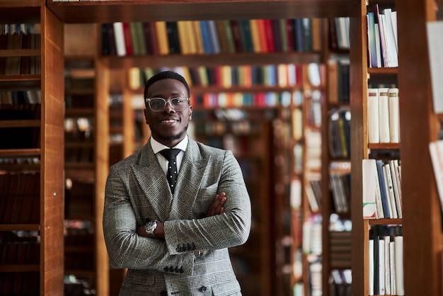Um homem afro-americano em um terno de negócio em pé em uma biblioteca na sala de leitura.