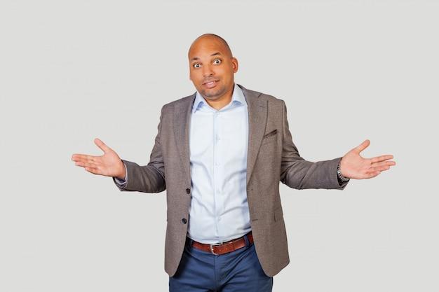 Um homem afro-americano encolhe os ombros, não sabe o que dizer em resposta, o que eles querem dele.