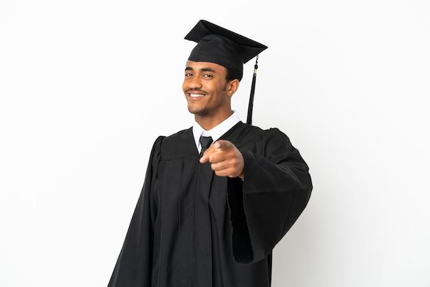 Um homem afro-americano graduado em uma universidade com um fundo branco isolado aponta o dedo para você com uma expressão confiante