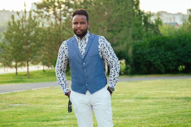 Um homem afro-americano jovem e bonito em um terno elegante em um parque de verão. empresário negro andando depois do trabalho no escritório.