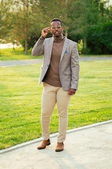 Um homem afro-americano jovem e bonito em um terno elegante em um parque de verão. empresário negro andando depois do trabalho no olhar de moda de escritório.