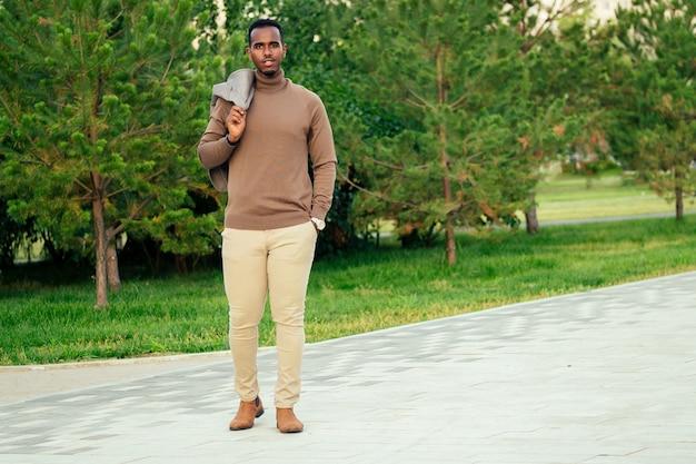 Um homem afro-americano jovem e bonito modelo elegante em um terno elegante em um parque de verão. empresário latino-americano hispânico negro posando para a sessão de fotos