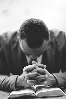 Um homem afro-americano solitário orando com as mãos na bíblia e a cabeça baixa