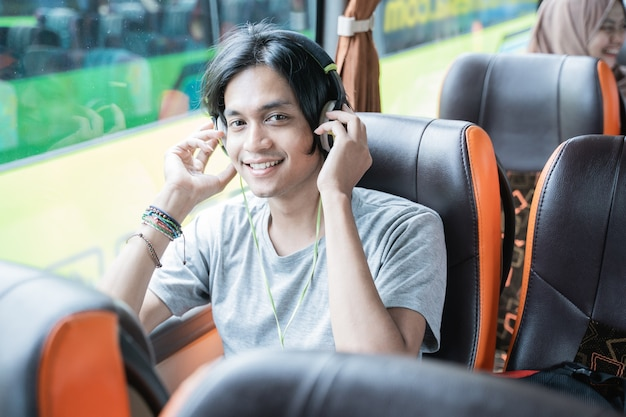 Um homem aisan usando fones de ouvido sorri enquanto ouve música enquanto está sentado perto da janela do ônibus