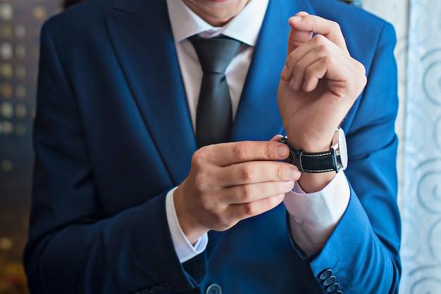 Um homem ajusta o relógio na mão closeup