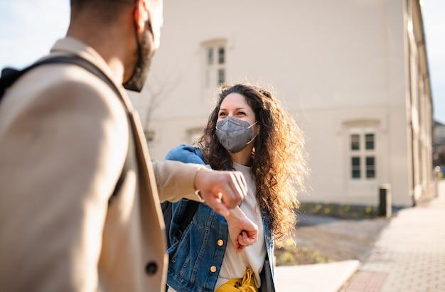 Um homem alegre e amigos mulher cumprimentando ao ar livre na cidade, coronavirus e de volta ao conceito normal.