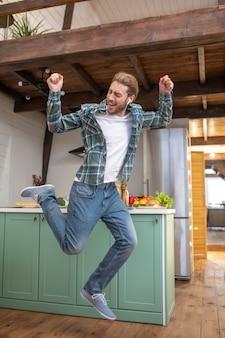 Um homem alegre e cheio de energia pulando em sua cozinha