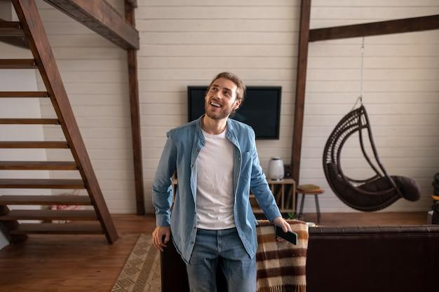 Um homem alegre segurando seu telefone enquanto está em seu apartamento