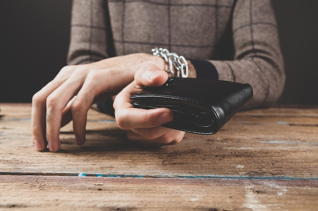 Um homem algemado segurando uma carteira em uma cena escura