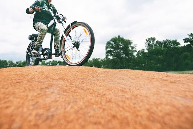 Um homem anda de bicicleta. caminhe pelo parque de bicicleta.