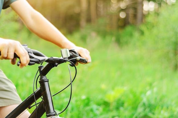 Um homem anda de bicicleta de montanha em uma estrada da floresta de verão