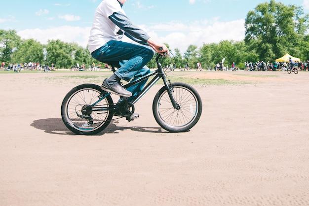 Um homem anda de bicicleta de montanha pequena em um dia ensolarado de verão. caminhe pelo parque de bicicleta. homem adulto em uma bicicleta infantil.