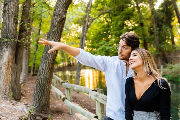 Um homem aponta o dedo para o lado enquanto abraça a namorada que o olha apaixonada.