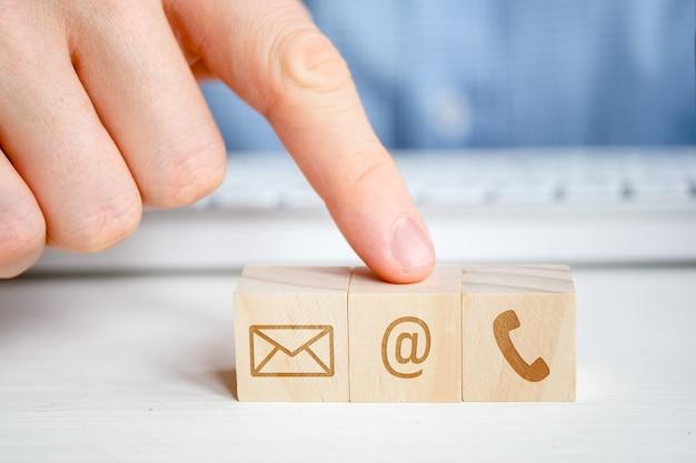 Um homem aponta para um cubo de madeira com a imagem de um símbolo de e-mail ao lado de um telefone e uma carta com a mão. contato para comunicação.