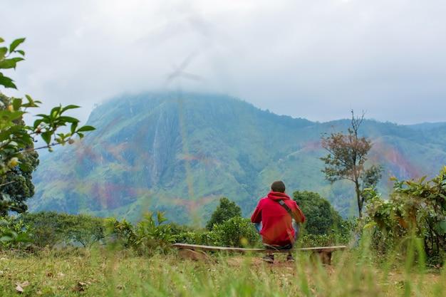 Um homem apreciando a paisagem montanhosa à beira de um precipício
