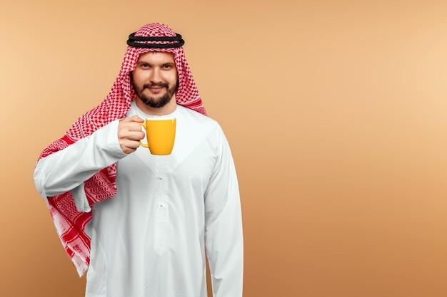 Um homem árabe segura em um traje nacional e segura uma caneca na mão. conceito de hospitalidade oriental.
