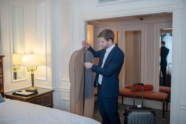 Um homem arrumando seu traje oficial para uma viagem de negócios