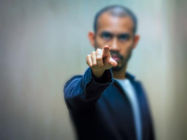 Um homem asiático aponta o dedo para a frente com uma expressão de raiva.
