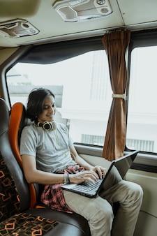 Um homem asiático com fones de ouvido e usando um laptop enquanto digita está sentado perto de uma janela no ônibus