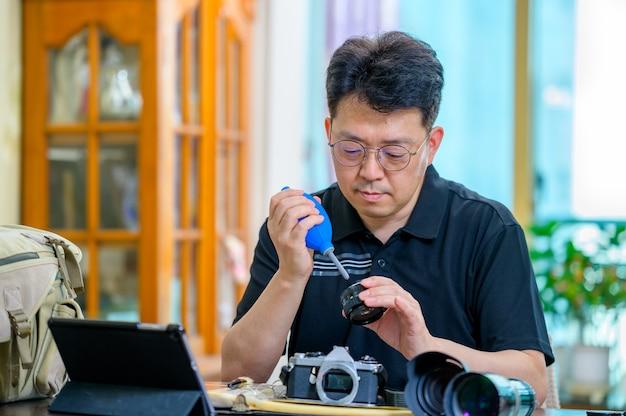 Um homem asiático de meia-idade cujo hobby é uma câmera slr de filme 35mm / 135mm