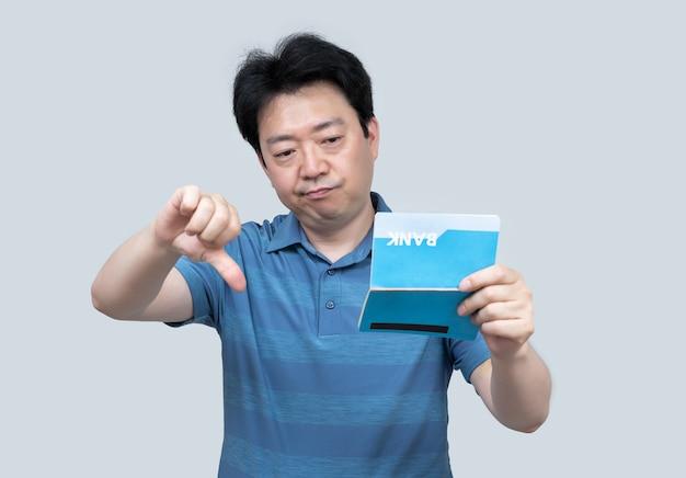 Um homem asiático de meia-idade, segurando uma caderneta bancária na mão