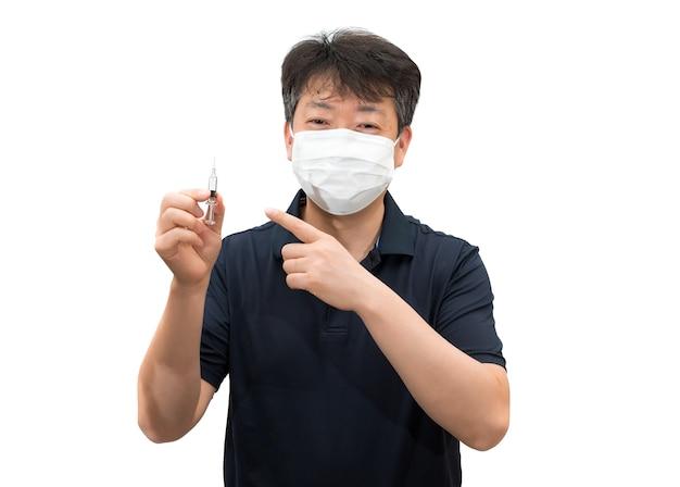 Um homem asiático de meia-idade usando uma máscara médica está segurando uma seringa de vacina na mão.