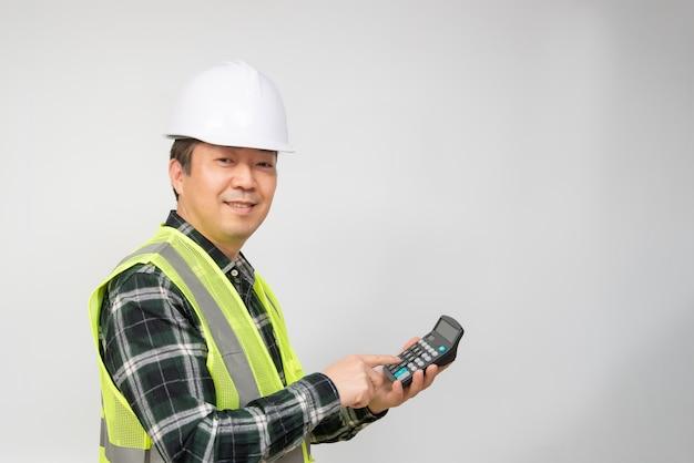 Um homem asiático de meia-idade, vestindo um boné branco e um terno de trabalho, segurando uma calculadora na mão.