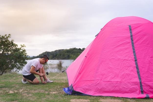 Um homem asiático em camiseta branca, definindo a tenda rosa no acampamento