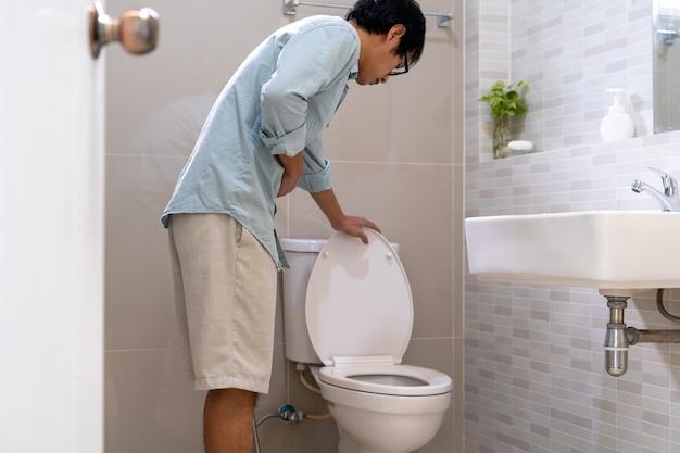 Um homem asiático em frente ao banheiro tem fortes dores abdominais.