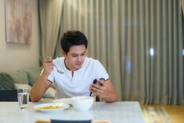 Um homem asiático está usando seu celular para bater um papo com seu amigo ou checando e-mail enquanto janta em casa à noite.