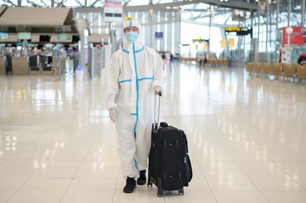 Um homem asiático está usando um traje de proteção pessoal no aeroporto internacional, viagens seguras, proteção covid-19, conceito de distanciamento social