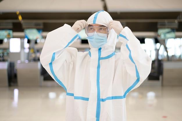 Um homem asiático está vestindo um terno de ppe no aeroporto internacional, viagens de segurança, proteção covid-19, conceito de distanciamento social.
