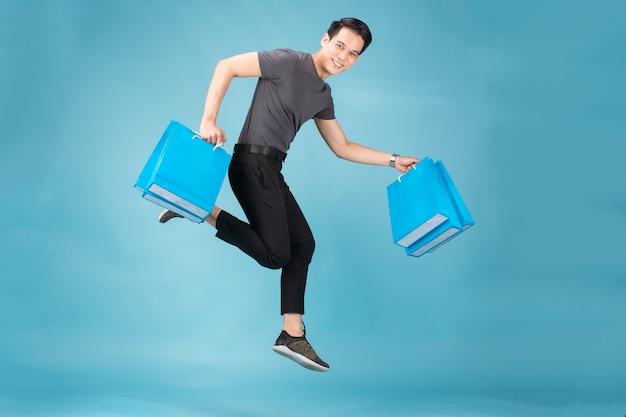 Um homem asiático pulando isolado sobre o fundo da parede azul segurando sacolas de compras