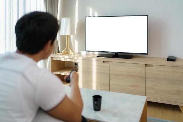 Um homem asiático segura um controle remoto de televisão e pressiona o canal enquanto assiste tv no sofá da sala de casa.