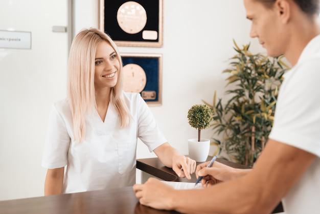 Um homem assina um papel com o consentimento para manutenção.