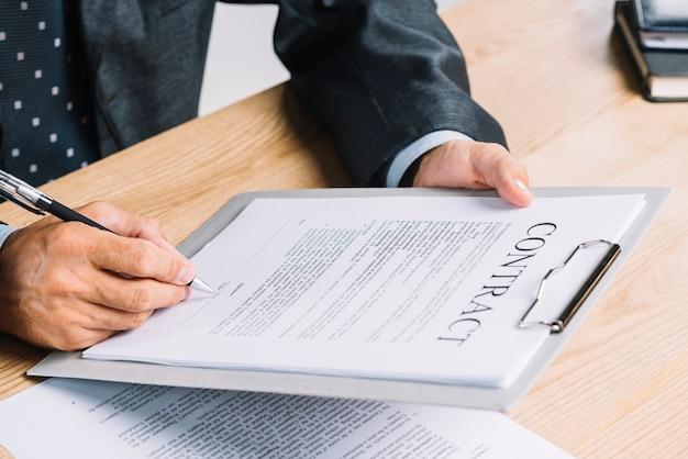 Um, homem, assinando, a, contrato, papel, anexar, ligado, área de transferência, ligado, a, tabela madeira