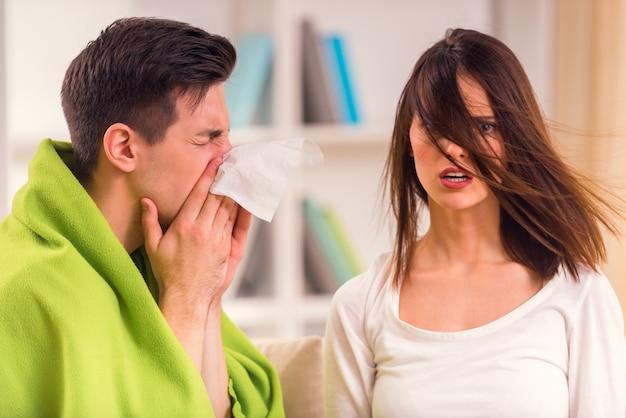 Um homem assoa o nariz em um guardanapo, enquanto uma garota se senta nas proximidades.