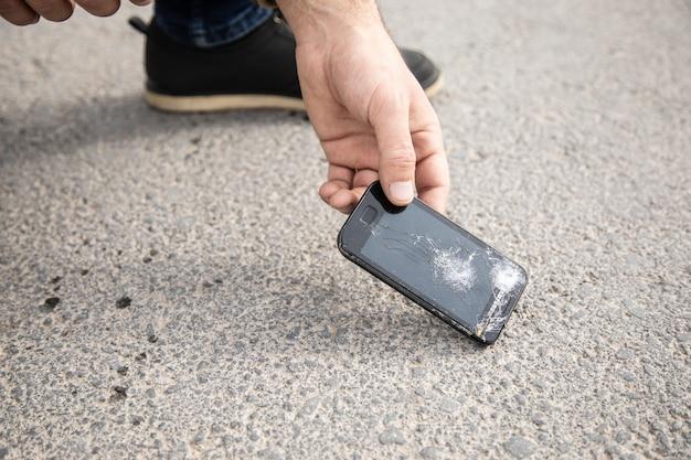 Um homem atende um telefone quebrado