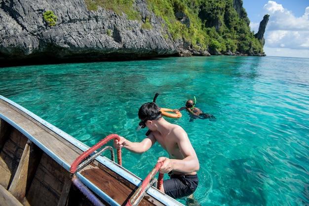 Um homem ativo em um barco tradicional tailandês está pronto para mergulhar e praticar snorkel, ilhas phi phi, tailândia