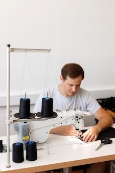 Um homem atraente atrás de uma máquina de costura na fábrica. borrão