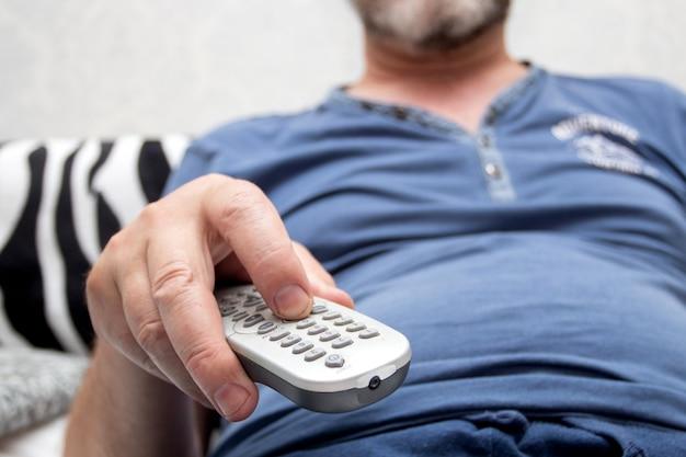 Um homem barbudo assistindo tv em casa com o controle remoto no sofá da sala
