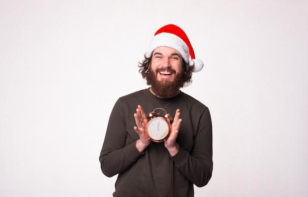 Um homem barbudo bonito sorrindo e mostrando que é época de natal em um despertador