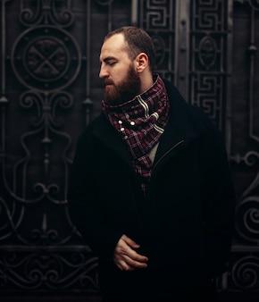 Um homem barbudo brutal bonito em uma jaqueta e cachecol fica perto de um portão de metal