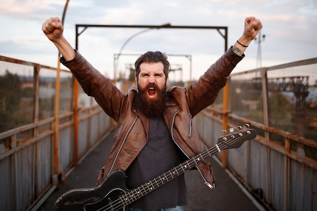 Um homem barbudo brutal, um guitarrista de bigode com uma jaqueta de couro marrom, levanta as mãos e grita com um violão