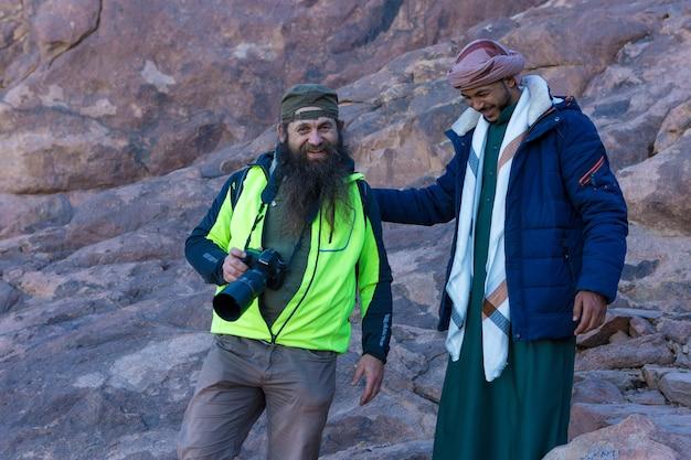Um homem barbudo com um beduíno africano na montanha de moisés com uma câmera