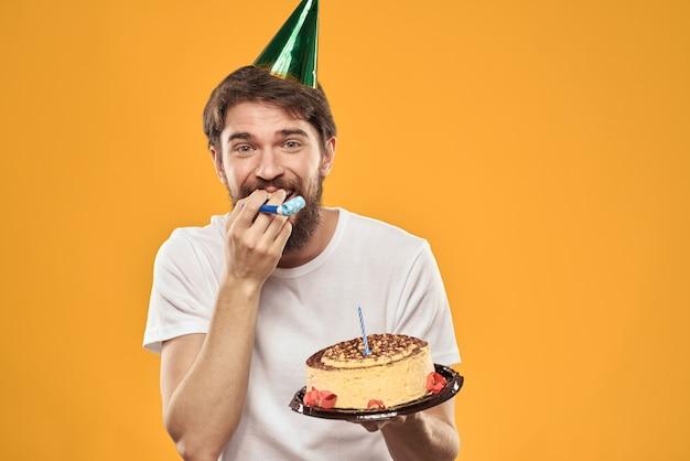 Um homem barbudo com um bolo e um boné comemorando seu aniversário