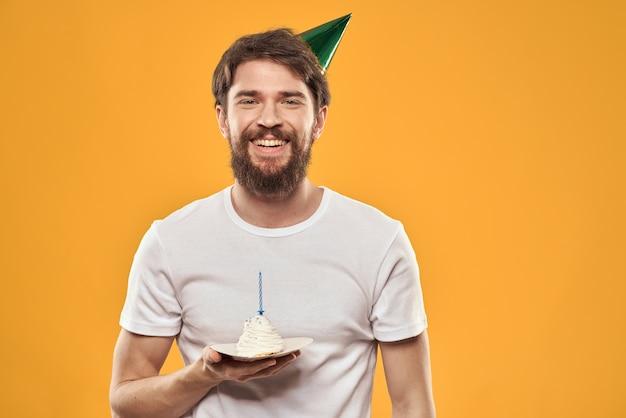 Um homem barbudo com um bolo e um boné comemorando seu aniversário.