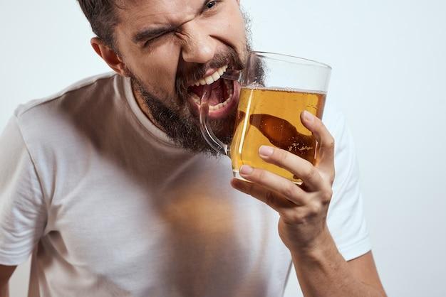 Um homem barbudo com uma caneca de cerveja em um espaço claro em uma camiseta branca cortou a vista de uma bebida alcoólica.