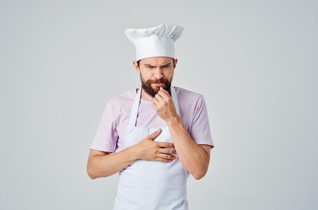 Um homem barbudo com uniforme de chef gesticula com as mãos as emoções de profissionais